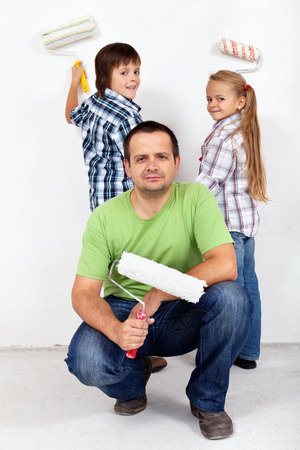 family activities: Kids and their father painting a room - holding paint rollers