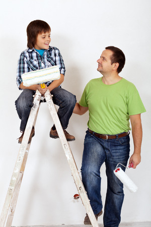 repaint: Father and son with painting utensils ready to repaint a room together Stock Photo