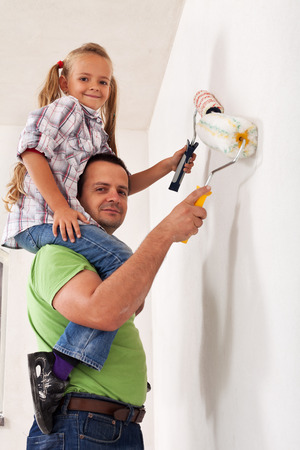 Happy father and little girl painting the room together -\ having fun with paint rollers