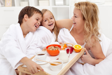 Happy morning - breakfast in bed for mom, kids pampering their mother Foto de archivo