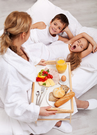 offsprings: Helthy breakfast in bed for the kids - a mother caring for her offsprings Stock Photo