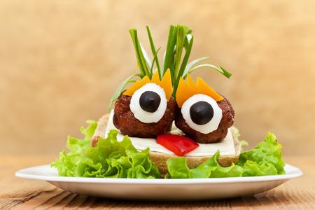 Sandwich aux boulettes de viande drôle avec des légumes, du fromage et laitue Banque d'images - 27425016