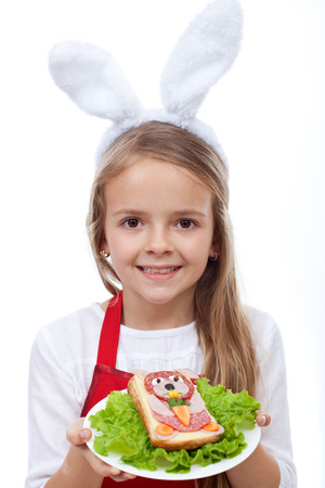 Happy bunny chef presenting her masterpiece - a rabbit shaped sandwich, isolated photo