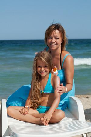 little girl beach: Woman and little girl using sunscreen cream - sitting on a beach chair Stock Photo