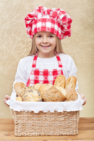 bakery products: Happy baker holding a basket with fresh bakery products