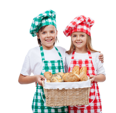 bakery products: Happy kids with chef hats holding basket with fresh bakery products - isolated Stock Photo