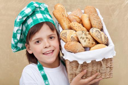 Happy baker boy holding basket with fresh bakery products - closeup photo