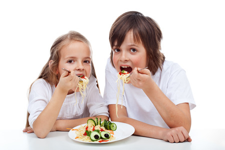 Kids eating a spaghetti dish with big appetite - isolated photo