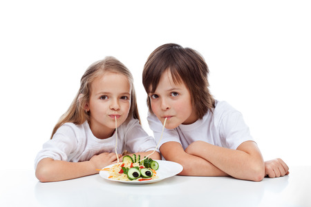 Kids eating a decorated spaghetti dish - isolated photo