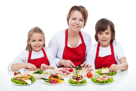mealtime: Woman and kids making creative food creature sandwiches together - isolated