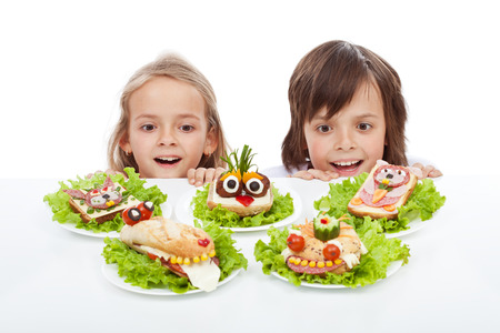Kids discovering the the healthy sandwich alternative - creative food creatures on plates photo