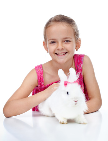 lionhead: Happy little girl with her cute white rabbit - isolated Stock Photo