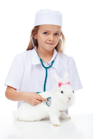 Little girl playing veterinary with her rabbit - care for our pets concept, isolated photo