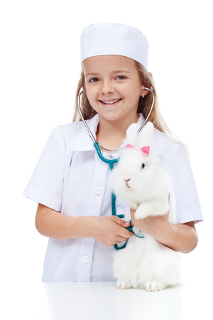 Little smiling girl playing veterinary with her rabbit - listening with a stethoscope photo