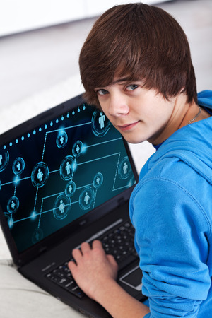 Teenager boy with laptop - connecting to social network application photo