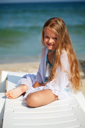 Little girl sitting on beach chair - by the sunny sea photo