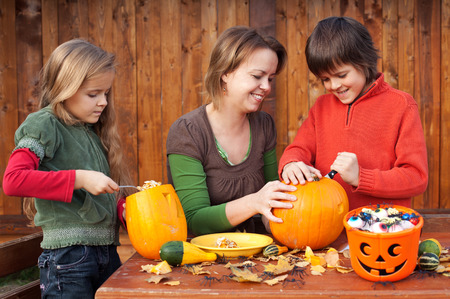 jackolantern: Woman helping kids to carve their pumpkin Halloween jack-o-lantern