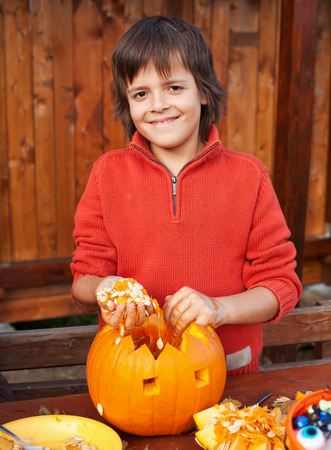 jackolantern: Closeup of boy carving a pumpkin Halloween jack-o-lantern - removing the seeds Stock Photo