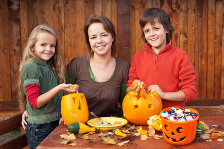 Happy woman and kids preparing for Halloween - carving pumpkin jack-o-lanterns
