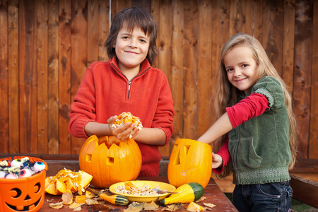 Kids carving their pumpkin jack-o-lanterns - removing the seeds photo