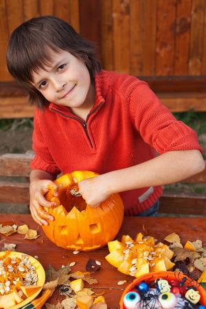 jackolantern: Boy preparing for Halloween - carving a pumpkin jack-o-lantern outdoors Stock Photo
