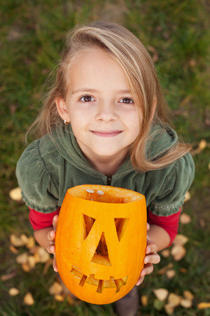 Autumn portrait with a Halloween pumpkin jack-o-lantern - little girl looking up photo