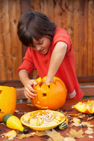 Boy busy carving a pumpkin jack-o-lantern for Halloween - removing the seeds