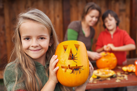 scary pumpkin: Little girl showing her freshly carved Halloween jack-o-lantern