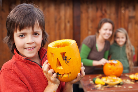 Family preparing for Halloween - boy showing his carved pumpkin jack o lantern photo