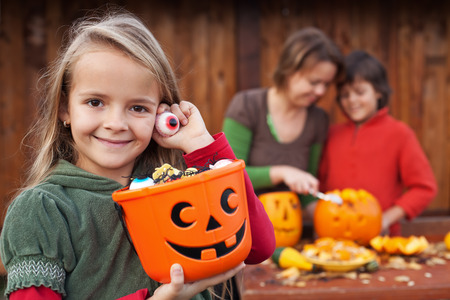 jack o lantern: Little girl preparing for the Halloween night with her family