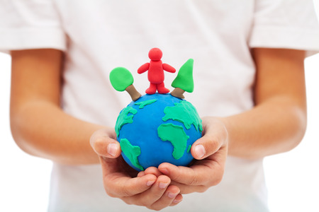 environmental awareness: Our environment and us concept with modelling clay earth in child hands