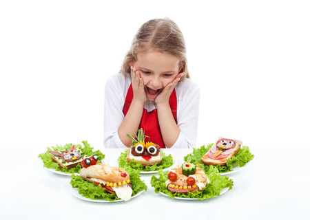 mealtime: Little girl with creative party sandwiches - fresh food creatures, isolated