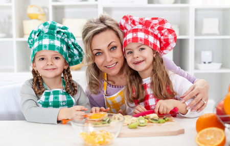 Happy chefs in the kitchen - woman and little girls portrait preparing fruit salad photo