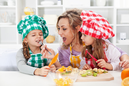 Woman and little girls preparing a fruit salad, tasting the ingredients - happy family moments photo