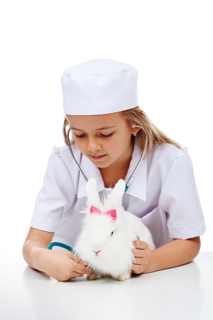 Little girl playing veterinary with her cute rabbit - using a stethoscope, isolated photo