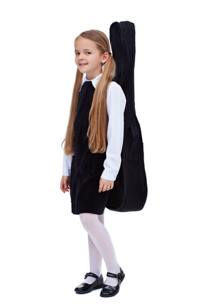 young schoolgirl: Little girl in elegant clothes carrying a guitar in a case - isolated