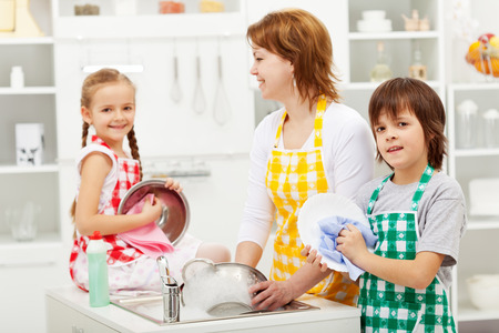 household tasks: Kids and their mother washing dishes in the kitchen Stock Photo