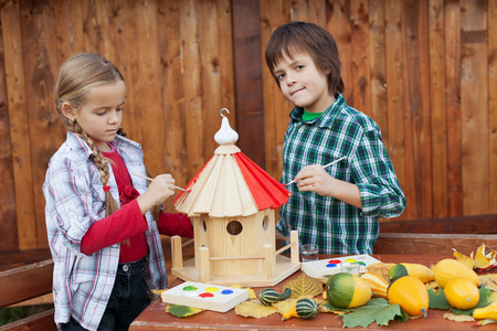 care providers: Kids painting a bird house in autumn Stock Photo