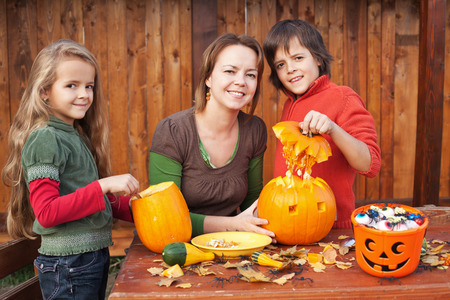 Kids carving jack-o-lanterns for Halloween - with a little help from their mother photo