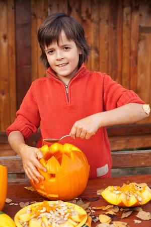 jackolantern: Boy carving his jack-o-lantern for Halloween - removing the seeds