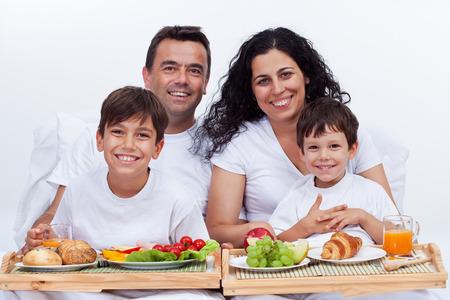 alimentacion sana: Familia feliz con dos ni�os que desayunan en la cama - una alimentaci�n saludable en el hogar