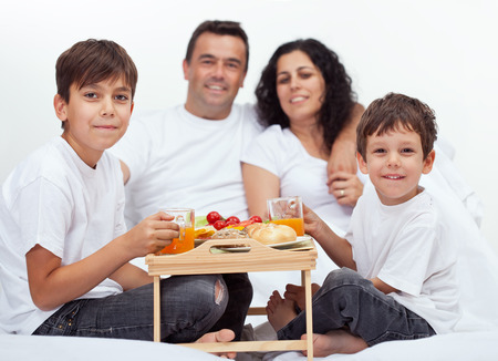 Family with two boys having breakfast in bed - with parents in background photo