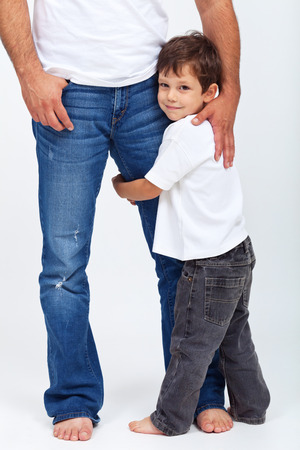 young parents: Small child holding his father leg - the safety provided by a parent Stock Photo