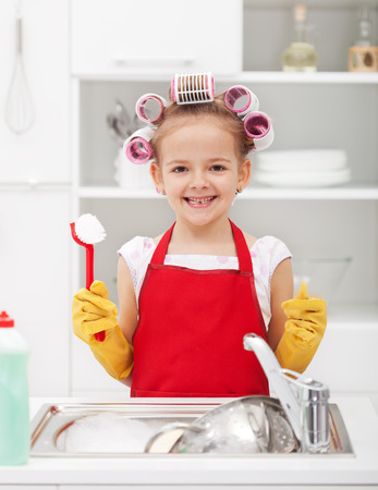 Happy housekeeping fairy - washing the dishes with a grin