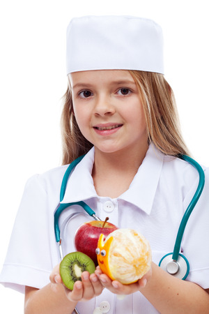 cretive: Little girl playing doctor - offering frsh fruits instead of medication, isolated