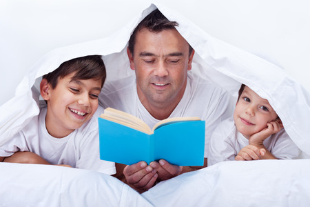 Father reading a story to his little sons - family time together Foto de archivo