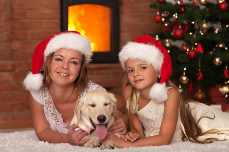 Christmas with our doggie - woman and little girl and the family pet Stock Photo