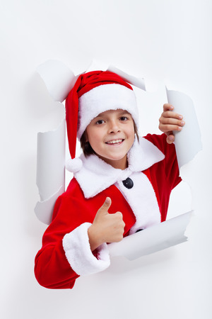 widening: Happy boy opening christmas season - widening a hole in white paper layer