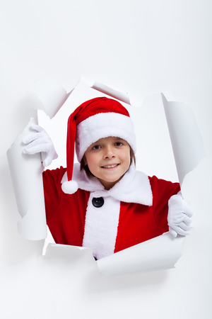 jagged: Opening the holidays season - boy looking through jagged edge hole in white paper layer