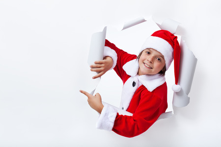 Happy Santa Claus costume boy pointing to copy space - christmas advertising photo